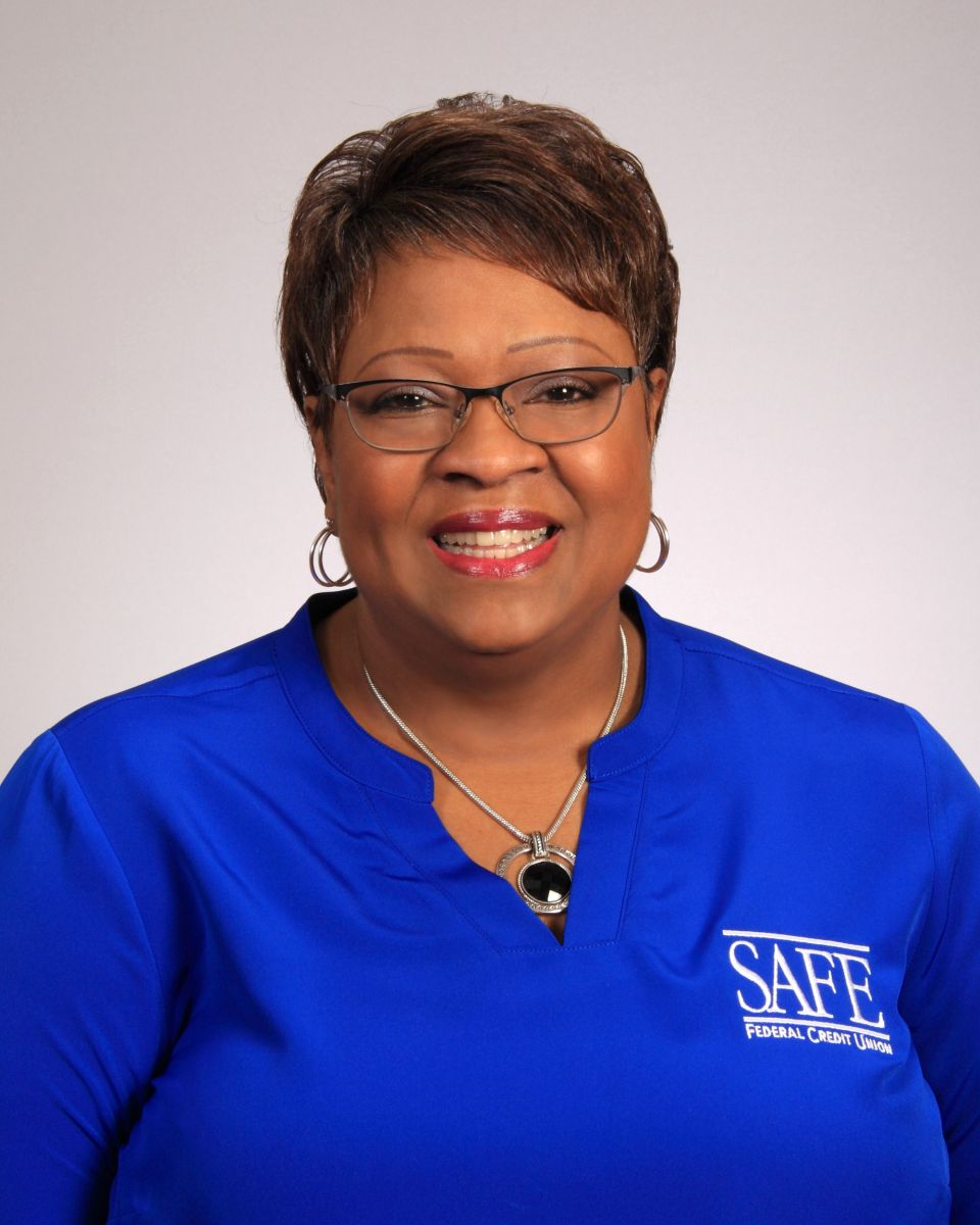 Donna Holmes wearing a blue top and glasses smiling