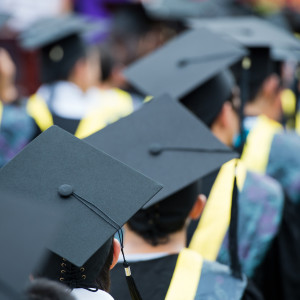 Students lined up to graduate, dressed in caps and gowns.