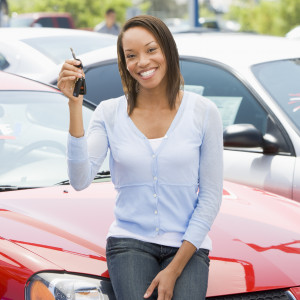 Woman holding keys to her new car.