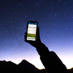 hand holding up smart phone in starry sky