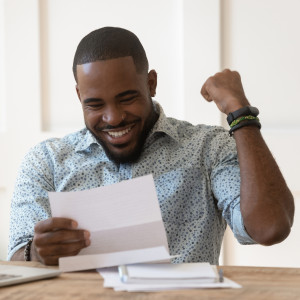Man wearing a light blue shirt reading his bank statement with excitement