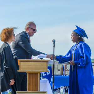 student wearing blue cap and gown accepting diploma
