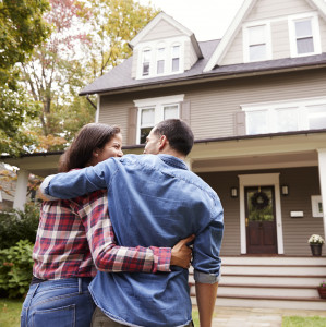 man and woman embracing in front of home