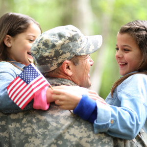 military man in uniform hugging two small children holding a miniature american flag