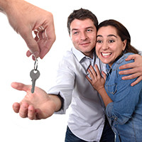 woman hugging man who is accepting keys in his hand