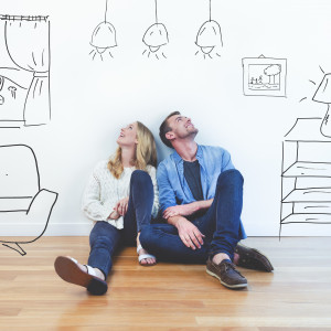 man and woman sitting on floor looking up at illustrations of home furnishings