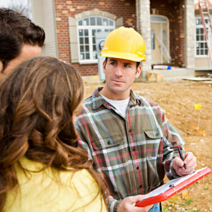 A contractor showing construction plans to the home owners