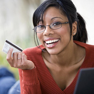 woman wearing red shirt and glasses holding credit card and smiling