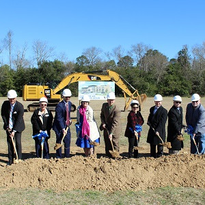 SAFE Federal Credit Union Dignitaries digging shovels into ground at the site of new building