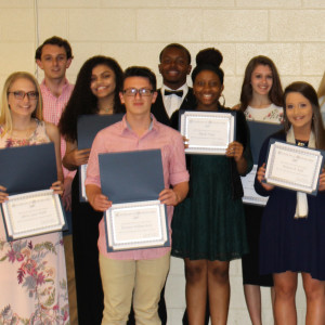 High School Students standing in 2 rows smiling and displaying their awards