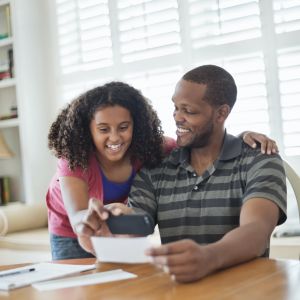 Father and daughter mobile banking together