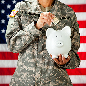 soldier in uniform putting money into a white piggy bank