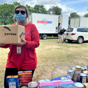 SAFE Employee wearing a pink shirt and mask carrying a box of donated food items. Shred truck is in the background.