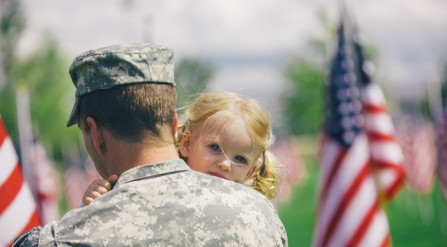 Military dad holding young daughter with American flags in the background.