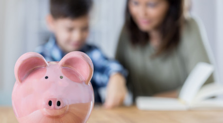 Mother and son saving in piggy bank.