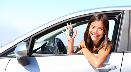 Woman leaning out from the window of a car, holding a set of keys