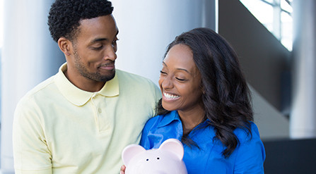 Couple smiling, woman holding a piggy bank