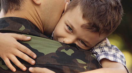 Little boy hugging his father, who is dressed in fatigues