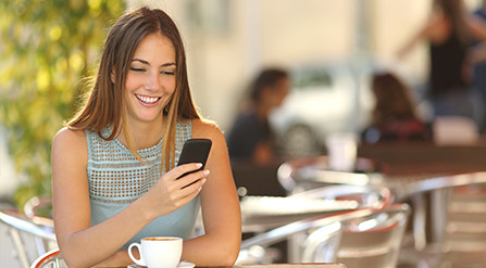 Woman sitting at a cafe, texting on her smartphone