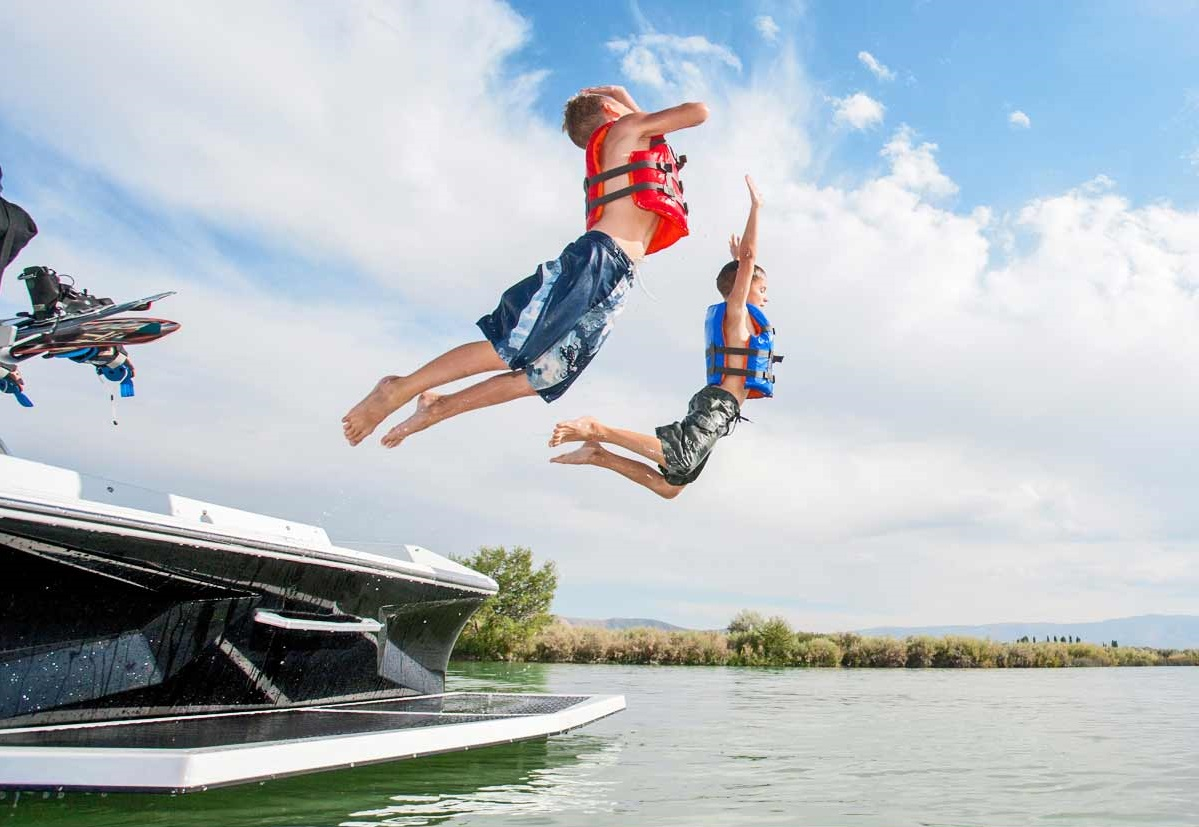 Two kids jumping off a boat.